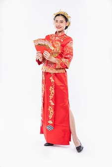Woman wear cheongsam suit and black shoe glad getting gift money from boss in chinese new year