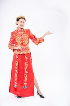 Woman wear cheongsam suit and black shoe glad getting new things for surprising in chinese new year