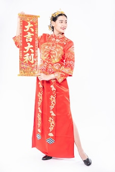 チャイナドレスを着た女性が家族に旧正月の幸運のために中国のグリーティングカードを贈る