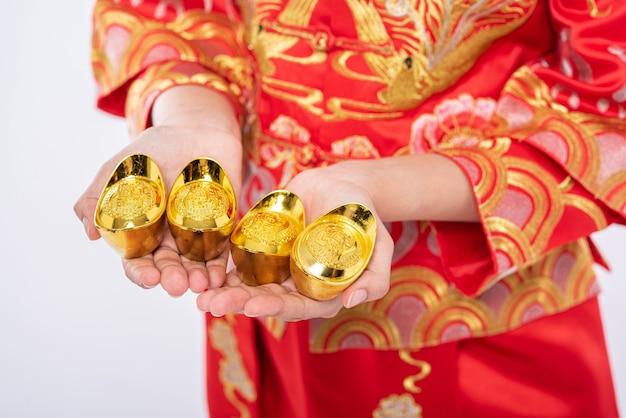 チャイナドレスを着た女性が中国の旧正月に幸運を祈って家族に金を贈る