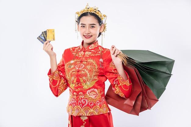 여자는 중국 전통 날에 신용 카드 쇼핑을 사용하여 행복하게 치파오 정장을 입는다.