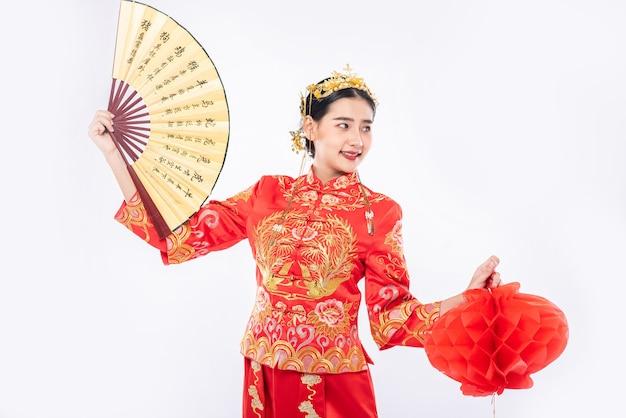 チャイナドレスを着た女性は、中国の旧正月の大きなイベントで示すために中国の扇子と赤いランプを保持します