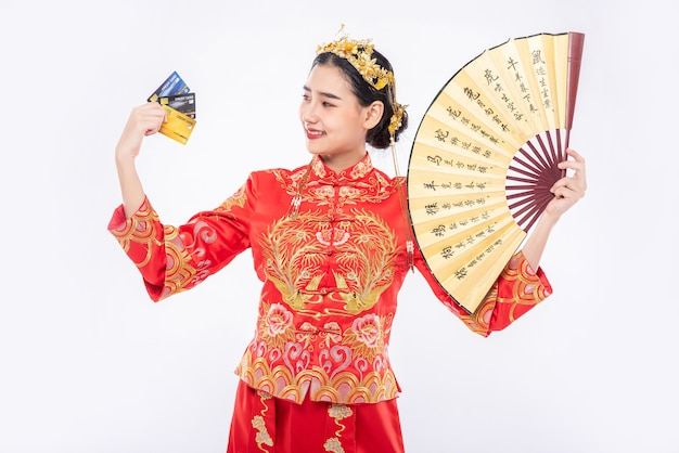チャイナドレスを着た女性が中国の扇子を持って、クレジットカードが中国の旧正月の買い物に使用できることを示しています