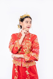 チャイナドレスを着た女性が中国の旧正月でイベント旅行者の買い物を促進するために写真撮影しています