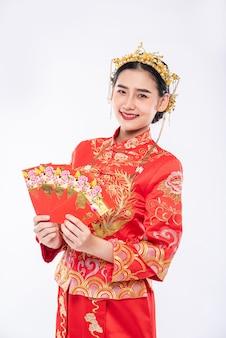 チャイナドレスを着た女性は、伝統的な日に両親から贈り物をもらうことができてとても幸運です