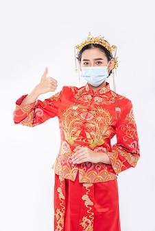 La donna indossa tuta e maschera cheongsam mostra il modo migliore per fare acquisti per proteggere le malattie
