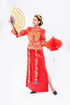 チャイナドレスを着た女性が中国の旧正月の大きなイベントで中国の扇子と赤いランプを宣伝する