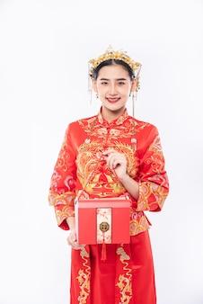 女性は伝統的な日に驚くべきために妹に赤いバッグを与える準備ができているチャイナドレスのスーツを着ています