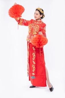 チャイナドレスの女性が中国の旧正月に彼女の店に赤いランプを飾るスーツショーを着用