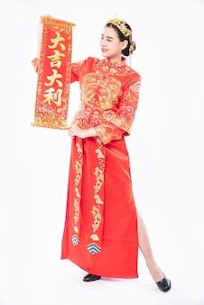 女性は中国の旧正月の幸運のためにチャイナドレスショー家族に中国のグリーティングカードを着用します