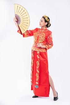チャイナドレスを着た女性が中国の旧正月の大きなイベントで中国の扇子を見せます