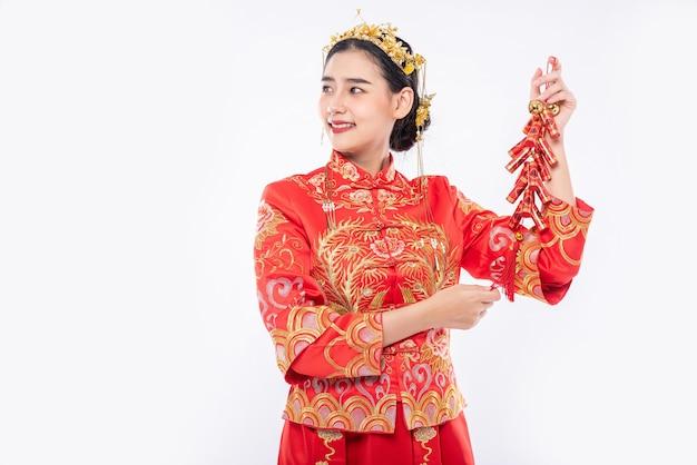 チャイナドレスを着た女性が中国の旧正月で販売するために爆竹をクライアントに見せます