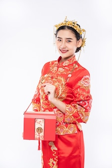 Woman wear cheongsam suit smile to get gift money from boss in chinese new year
