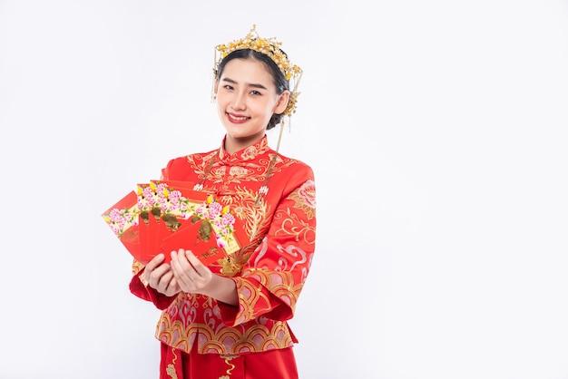 La donna indossa il sorriso del vestito cheongsam per ottenere i soldi del regalo dal capo nel capodanno cinese