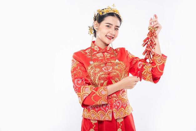 女性は中国の旧正月で上司から爆竹を取得するためにチャイナドレスのスーツの笑顔を着ています