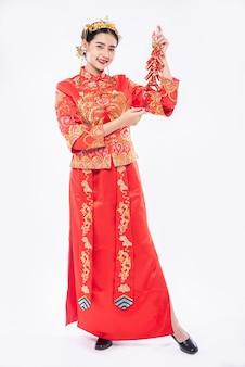 女性は中国の旧正月の親戚から爆竹を取得するためにチャイナドレスのスーツの笑顔を着ています