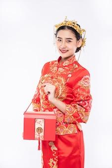 여자는 중국 새해에 상사로부터 선물 돈을 받기 위해 치파오 정장 미소를 입는다.