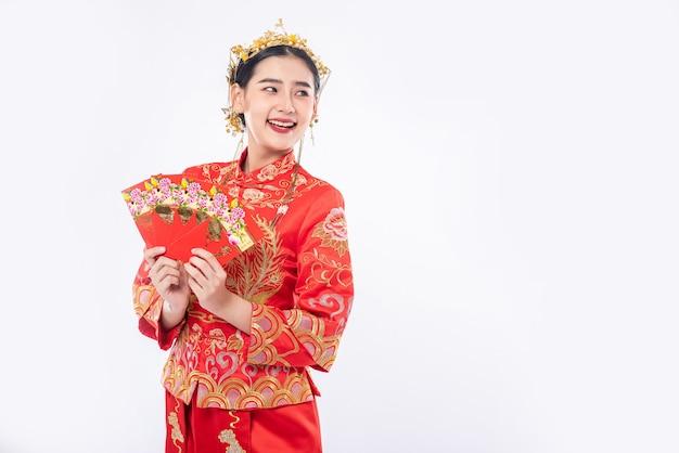 女性は中国の旧正月に家族から贈り物のお金を得るためにチャイナドレスのスーツの笑顔を着ています