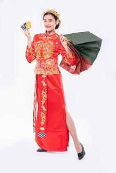 女性は中国の旧正月でクレジットカードの買い物を使用するためにチャイナドレスのスーツの笑顔を着ています