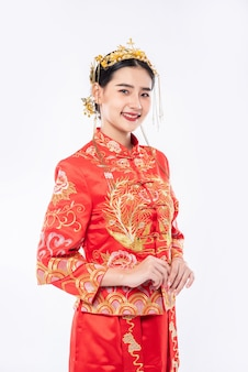 女性は中国の旧正月で買い物をする旅行者を歓迎するためにチャイナドレスの笑顔を着ています