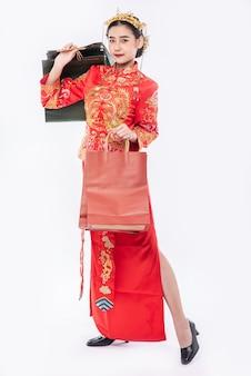 여자는 중국 새해에 쇼핑에서 종이 봉지로 치파오 정장 미소를 입는다.