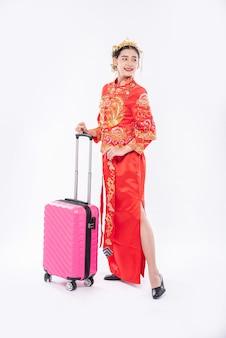 女性は中国の旧正月にピンクのトラベラーバッグで旅行する準備ができて王冠とチャイナドレスのスーツを着る