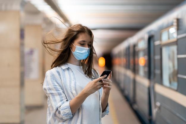 플랫폼에서 지하철을 기다리는 소셜 미디어에서 휴대폰 채팅으로 얼굴 마스크를 쓴 여성