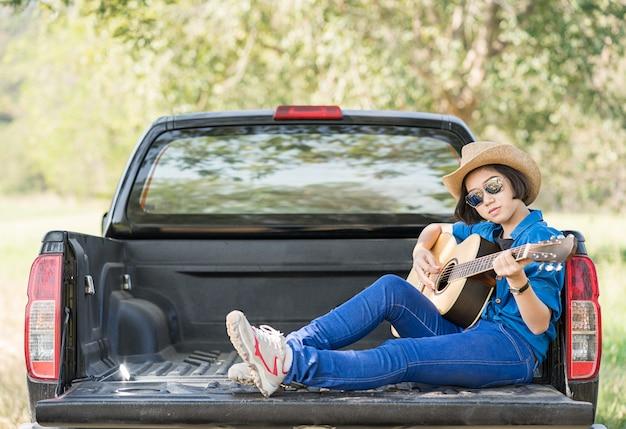 女性着用帽子とピックアップトラックでギターを弾く