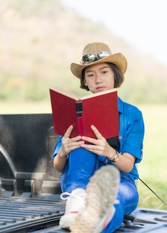 Woman wear hat and reading the book on pickup truck