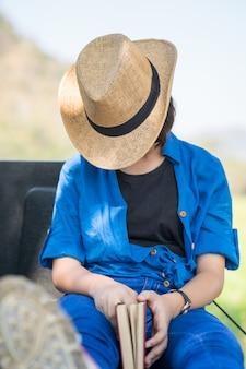 Woman wear hat sit sleep in countryside