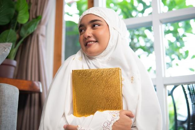 コーランを保持しているヒジャーブを着ている女性