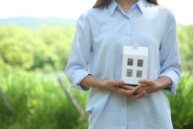 Woman wear light blue shirt with holding house