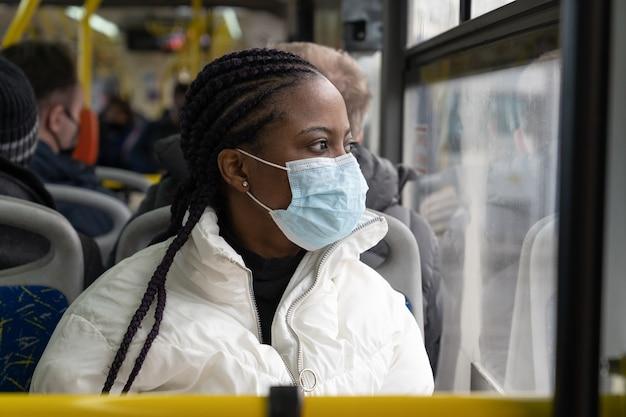 여자는 covid의 새로운 정상에 대중 교통 버스에서 의료 마스크 여행을 착용