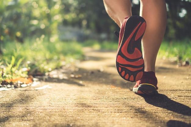 여자는 산책과 자연 녹색 배경에서 실행에 실행 신발을 착용. 건강 운동 개념입니다.