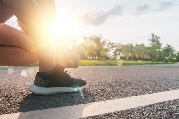 女性はウォーキングやランニングに自然の緑の背景にランニングシューズを着用します。健康運動。