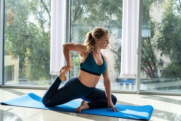 女性は健康のためにヨガを練習しているスポーツ服を着て、家の窓の近くの背中の痛みを和らげるのを助けます