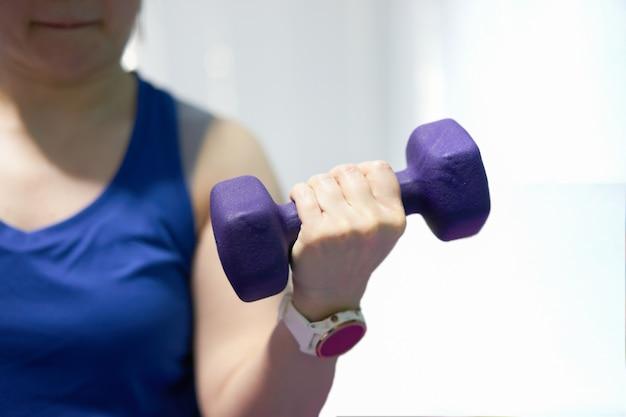 女性はスポーツウォッチホールドリフティングダンベル片手力唇上腕二頭筋ウェイトトレーニング屋内ぼかし背景を着用