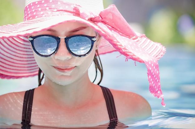 Woman wear sunglasses in pool.