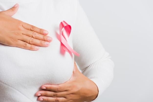女性はtシャツを着て、胸にピンクの乳がん啓発リボンをつけ、手で胸を押さえています