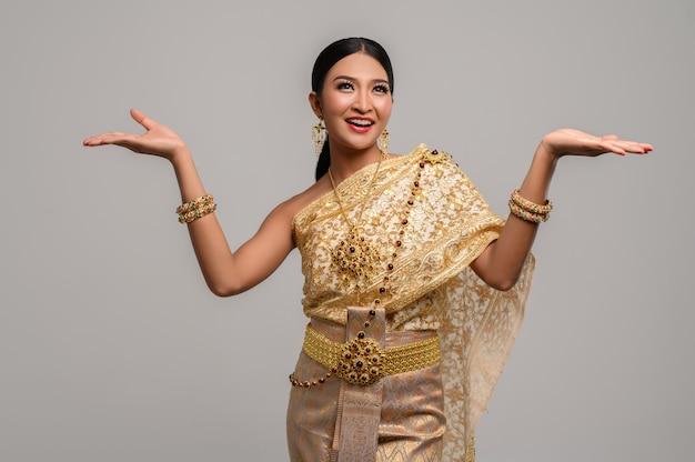 Женщина носит тайскую одежду и раскрывает руки с обеих сторон.