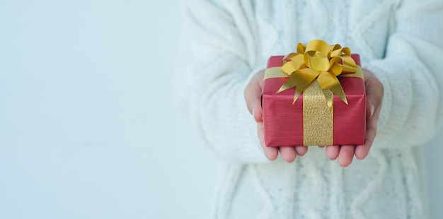 Woman wear white cardigan sweater and hold red gift box with gold ribbon on white color background