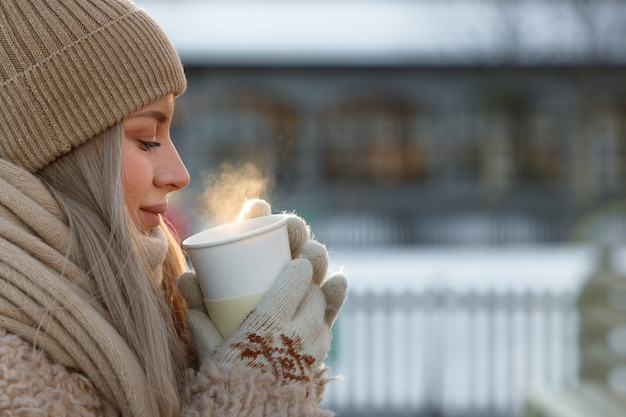 Woman wear white mittens holding steaming white cup of hot coffee or tea in cold winter sunny day