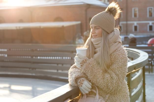 女性は寒い冬の晴れた日に熱いコーヒーやお茶の蒸し白いカップを保持している白いミトンを着用します