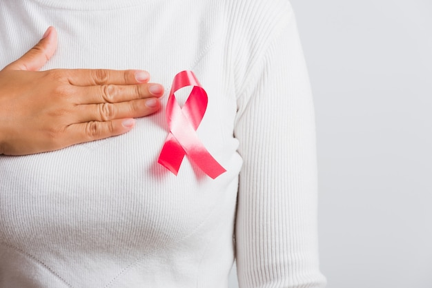 女性は白いシャツを着てピンクの乳がん啓発リボンを持っており、胸にハンドルを使用しています
