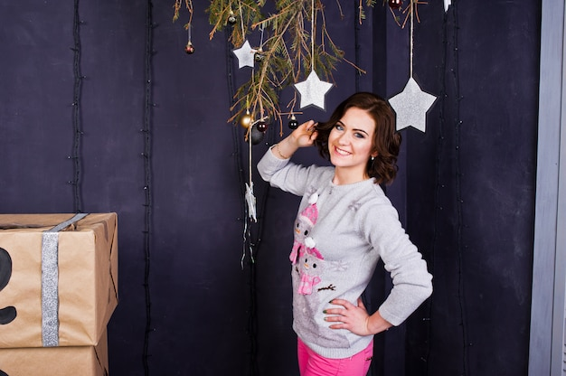 Woman wear on winter sweaters at room with christmas decorations.