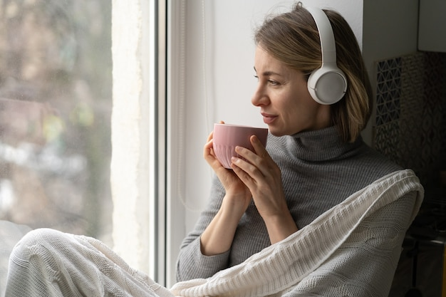 Woman wear wireless headphones, listening to music, sitting on the windowsill, looking at window