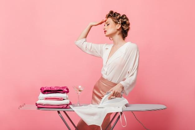 Женщина устало позирует на розовой стене во время глажки одежды