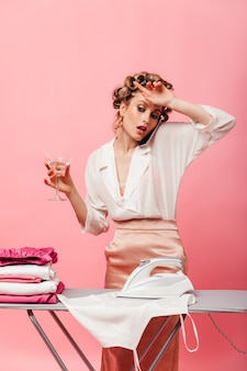 Woman wearily wipes her brow during time of ironing clothes