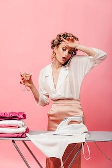 La donna si asciuga stancamente la fronte durante il tempo di stirare i vestiti