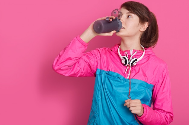 ボトルから水とバラのスポーツウェア飲料水を身に着けている女性、バラ色の分離したモデルのポーズ。若い女性フィットネスインストラクターまたはスタジオのパーソナルトレーナー。